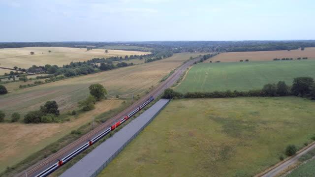 fast commuter train meandering through the countryside - intercity filmów i materiałów b-roll