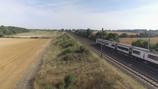 fast commuter train speeding through the countryside during summer - intercity filmów i materiałów b-roll