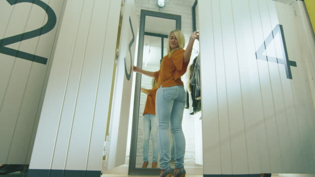 Fast cut-out footage of a blond girl trying different clothes in a fitting room. video