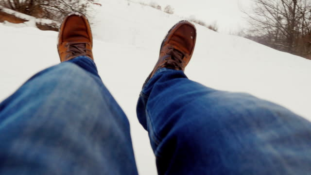 Fast descent from the snowy mountains. In the picture visible male legs in boots. POV video video