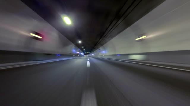 vídeos de stock e filmes b-roll de fast driving at a empty tunnel.vehicle shot - alfalto