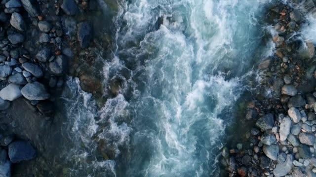 vídeos de stock e filmes b-roll de fast flowing river with a mountain range in the background. - noruega