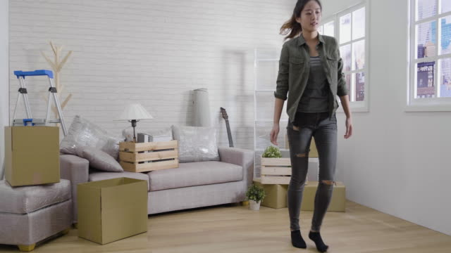 vídeos de stock e filmes b-roll de fast forward of two asian young girls roommates bringing cardboard boxes with things in new apartment. busy women move carton container with stuff into bright modern new house. female carry parcels. - engradado