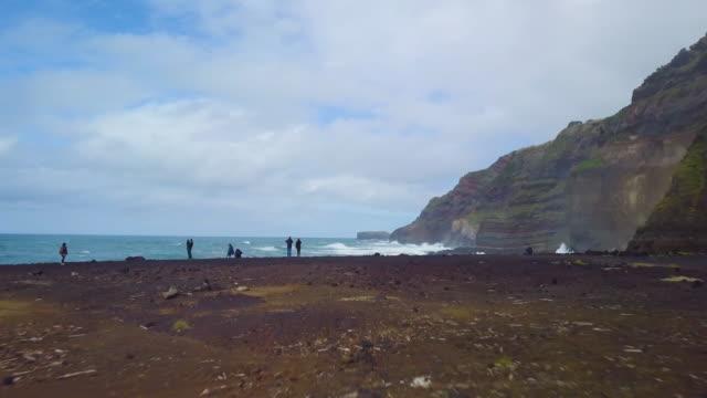 vídeos de stock e filmes b-roll de fast forwarding drone shot of people taking photos of beautiful waves crashing at cliff - arquipélago
