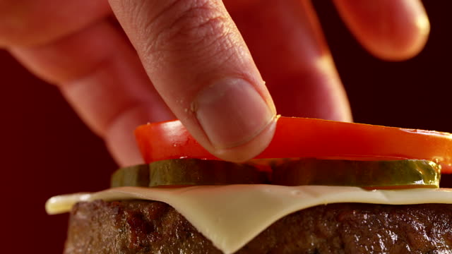 fast making of a burger. shot on red epic cinema camera. - cheeseburger filmów i materiałów b-roll