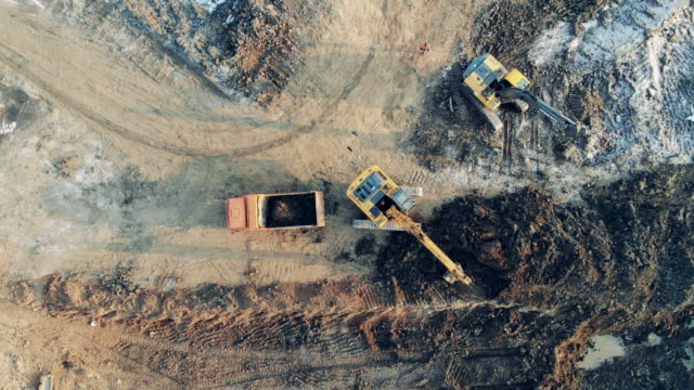 Fast motion of working process at the extraction site in a top view. Heavy industrial equipment working. Fast motion of working process at the extraction site in a top view. 4K mining natural resources stock videos & royalty-free footage