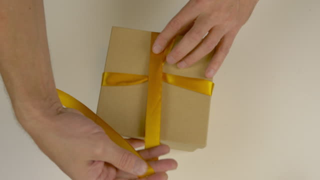 fast motion time lapse. wrapping gift box. caucasian mans hands packing gift box. mens hands tie a ribbon around a brown cardboard box. top view close up. gold yellow tape ribbon. - триллиум стоковые видео и кадры b-roll