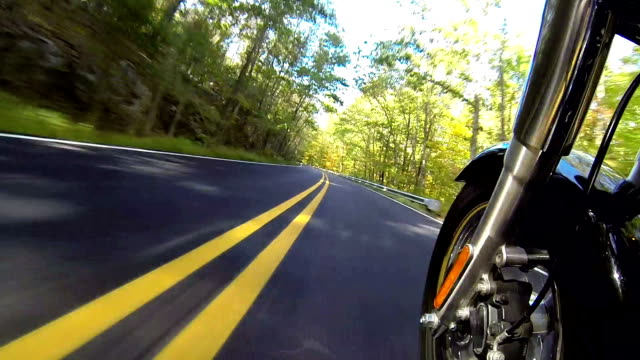 Fast Motorcycle Ride, camera side view mounted Fast motorcycle ride on a two lane country road speeding by trees and double yellow line. Camera point of view mounted on side of bike with forks and wheel visible.  motorcycle stock videos & royalty-free footage