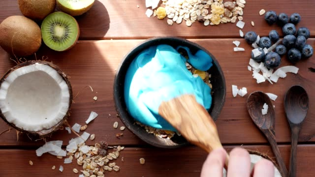 fast movie, making blue majik superfod smoothie bowl above view, flatlay video