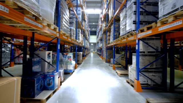 Fast moving camera between several aisles between metal racks. video