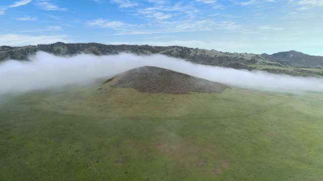 Fast moving low cloud coming from the Pacific Ocean around the hills in San Simeon, California, nearby Cabrillo Highway, and Arroyo Del Oso. The windy sunny spring day. Aerial drone video with the panning camera motion.