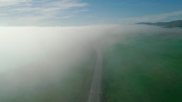 Fast moving low cloud coming from the Pacific Ocean around the hills in San Simeon, California, nearby Cabrillo Highway, and Arroyo Del Oso. The windy sunny spring day. Aerial drone video with the slow panning camera motion.