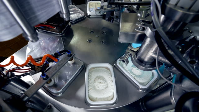 Fast moving robotized packing, sealing and labelling of curd. video