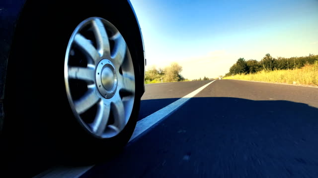 Fast speed car wheel spinningon rural road asphalt, Point of View