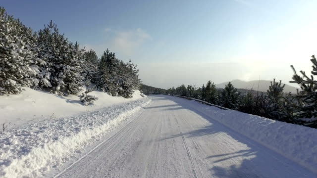 Fast sport car drive on winter snow road, mountain uphill video