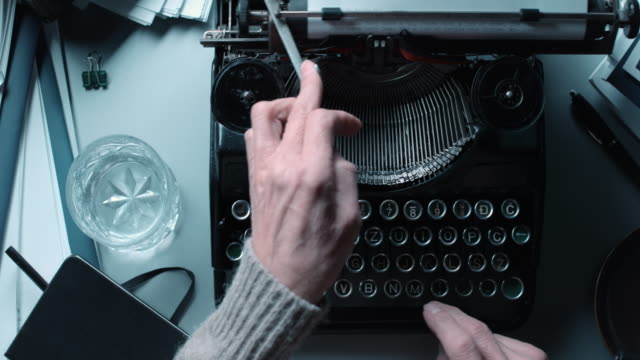 DS Fast typing on old typewriter behind stacked office desk Medium right above dolly shot of a person working fast on an old typewriter behind a desk full of papers and an old phone by the side. typewriter stock videos & royalty-free footage