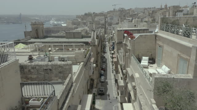 Fast Vertical descent, drone flying narrow beautiful old street, Valletta, Malta. Old, vintage windows, balconies. - 4K