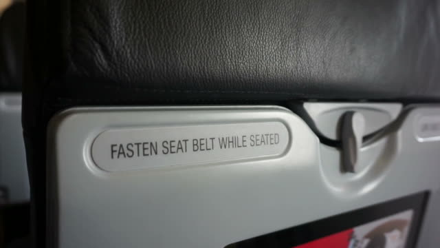 Fasten seat belt while seated and life vest under the seat sign across airplane seating. Abstract safety video
