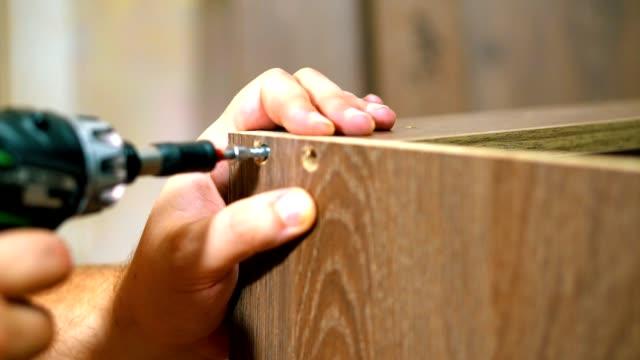 fastening the panel with a screw using a screwdriver. hand screwdriver in operation. furniture - wkręt filmów i materiałów b-roll