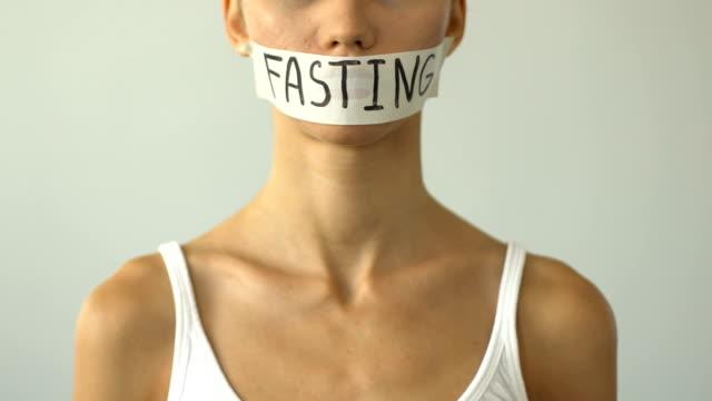 fasta på tejpade munnen av smal tjej, begreppet malnutrition, anorexi - fasta bildbanksvideor och videomaterial från bakom kulisserna