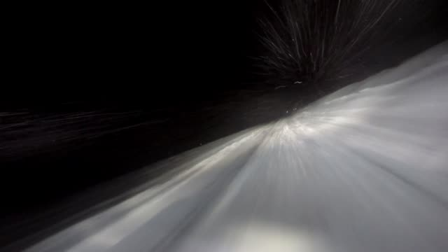 Fast-moving car in winter with snow flying toward headlights