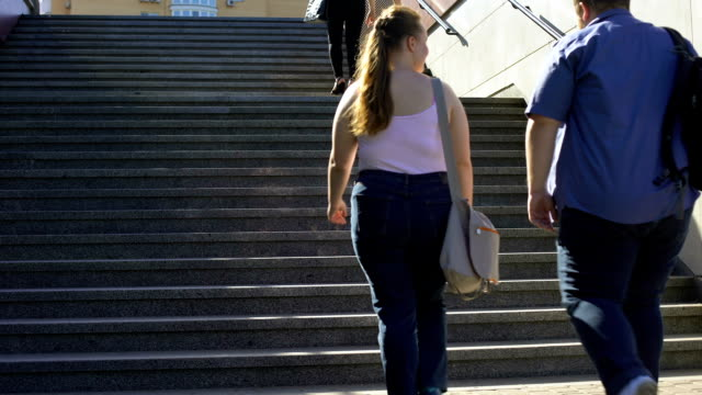 fat couple walking together on stairs, problems of overweight among young people - тяжёлый стоковые видео и кадры b-roll