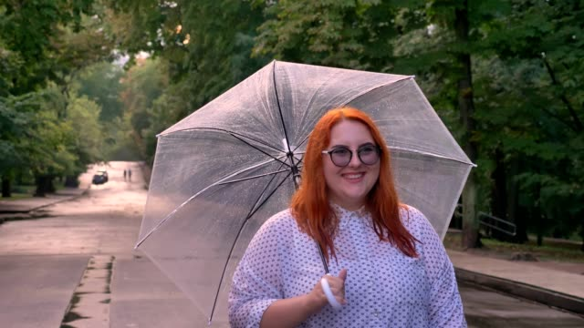 Fat ginger girl with glasses is going on road in park in rainy weather, holding umbrella