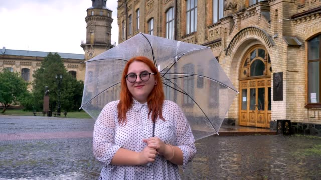 Fat ginger girl with glasses is standing in park in rainy weather, holding umbrella, watching at camera, smiling, building on background