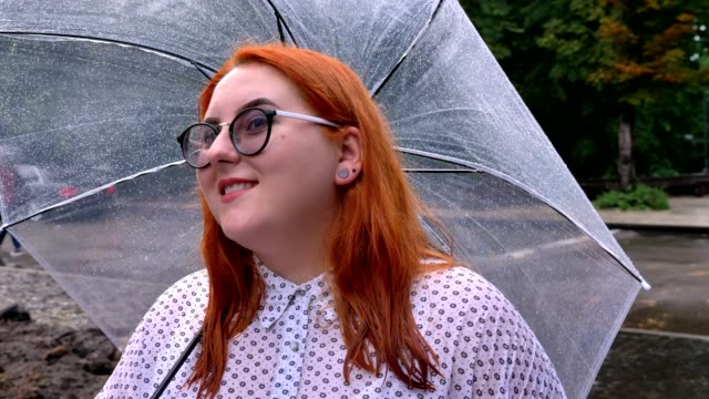 Fat ginger girl with glasses is standing in park in rainy weather, holding umbrella, going to building