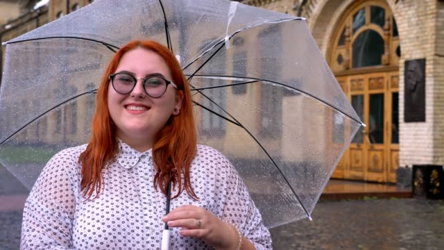 Fat ginger girl with glasses is standing in rainy weather, holding umbrella, watching at camera, smiling, building on background