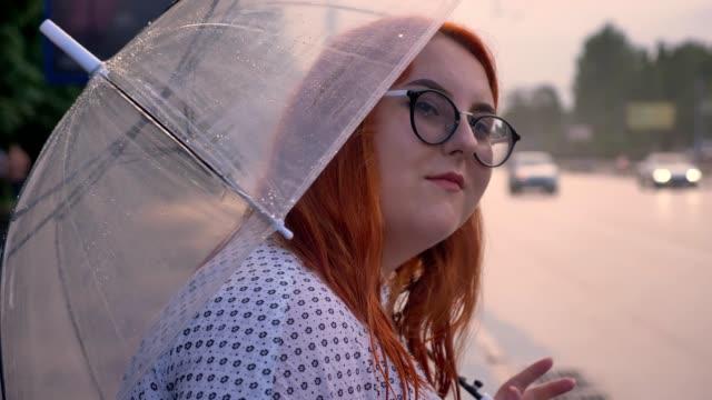 fett ingwer mädchen mit brille ist bei regenwetter in bushaltestelle stehend, beobachtete autos, hält regenschirm - kräftig gebaut stock-videos und b-roll-filmmaterial