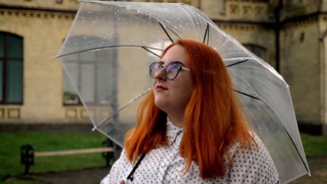 Fat ginger girl with glasses is walking in park in rainy weather, holding umbrella, side view