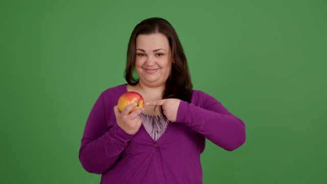 A fat girl eating an apple on a green background video