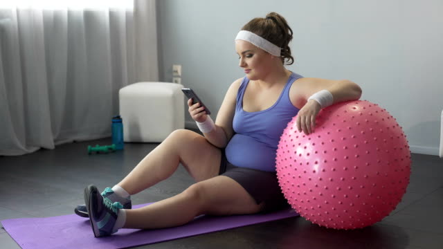 Fat lady checking results of online slimming marathon after workout, mobile app Fat lady checking results of online slimming marathon after workout, mobile app fat nutrient stock videos & royalty-free footage