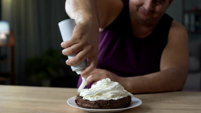 Fat male decorating cake with whipped cream and putting cherry on the top video