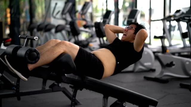 dicker mann tun, sitzen-ups in turnhalle - muskulös stock-videos und b-roll-filmmaterial