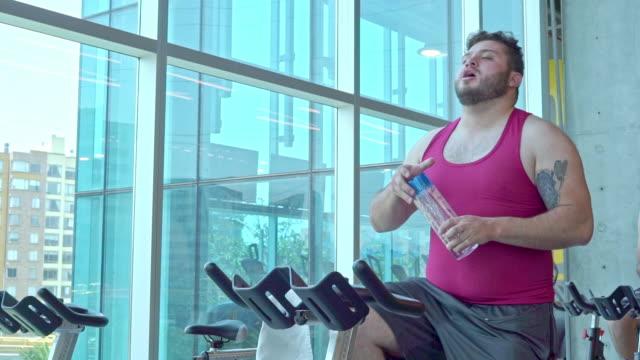 fetter mann, der auf der übung trainiert - lateinische schrift stock-videos und b-roll-filmmaterial