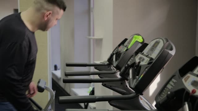 Fat man gets on the treadmill in the gym Fat man gets on the treadmill in the gym water wastage stock videos & royalty-free footage