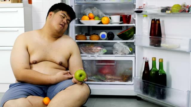 l'uomo grasso è seduto accanto al frigo e sta dormendo. - avidità video stock e b–roll