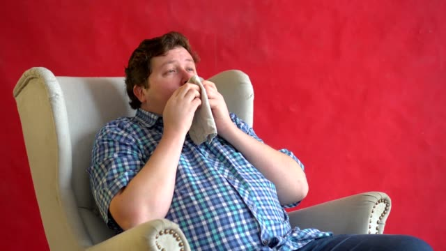 Fat man isolated over a red background is sneezing in the handkerchief video