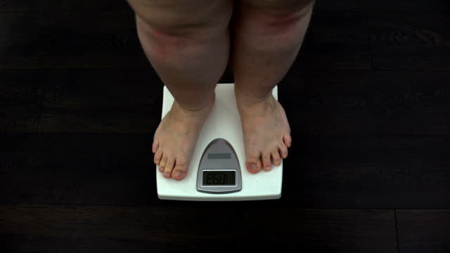 fat man measuring weight on scales at home, obesity problem, sedentary life - sovrappeso video stock e b–roll