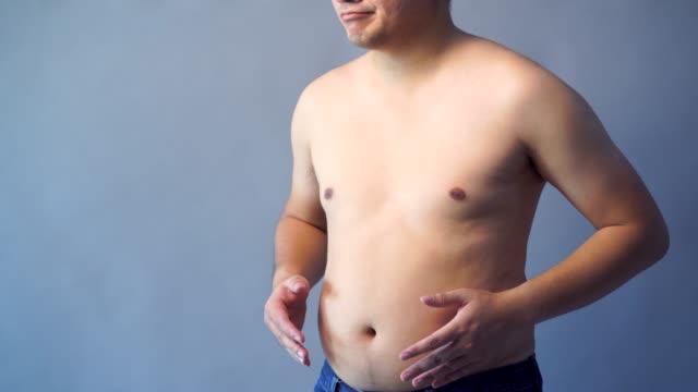 デブ男の手持ち株脂肪腹、分離の背景、灰色の背景色に太りすぎ。 - 肥満点の映像素材/bロール