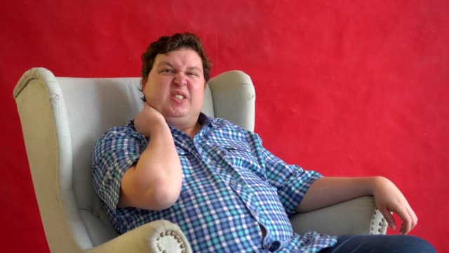 Fat man sit on chair with neck pain isolated on red background video