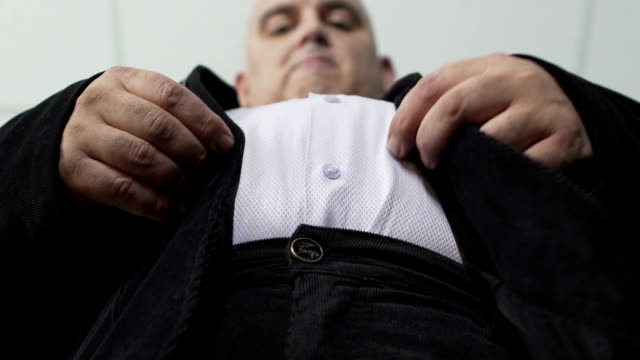 Fat man trying to fasten a button on his jacket, extra weight, bottom view video