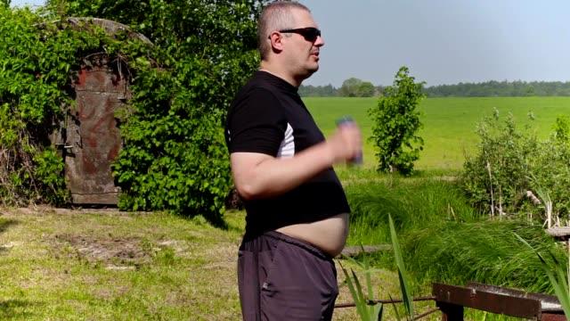 vídeos de stock e filmes b-roll de gordura homem com halteres, ao ar livre pequena - peso equipamento para exercícios