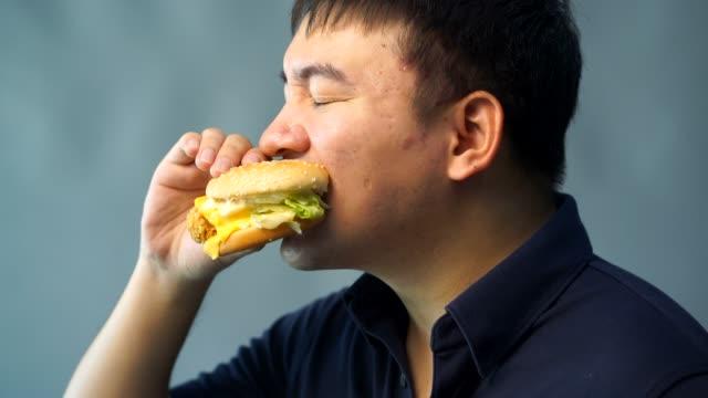 뚱뚱한 남자는 햄버거를 먹고 있다. 행복 하 게 - burger and chicken 스톡 비디오 및 b-롤 화면