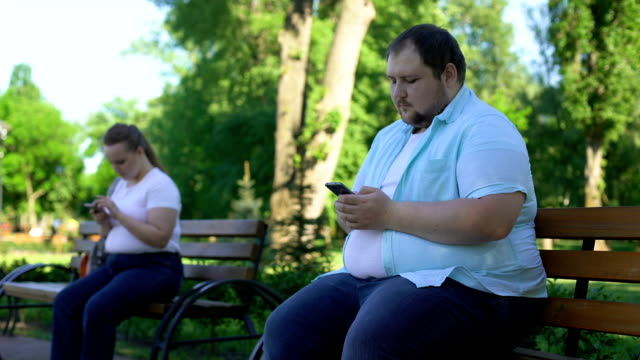 Fat people easy communicate in social network but afraid acquaintance in reality Fat people easy communicate in social network but afraid acquaintance in reality park bench stock videos & royalty-free footage