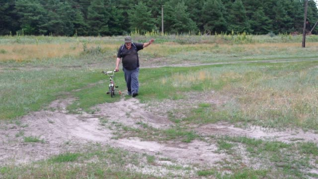 Fat senior man walks on a country road driving the grandchild's tricycle video