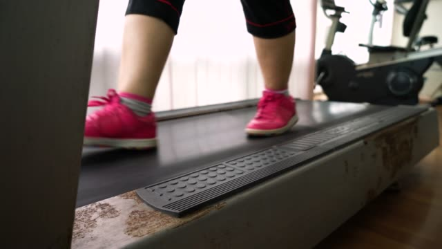 fat woman walking on treadmill - runner rehab gym video stock e b–roll