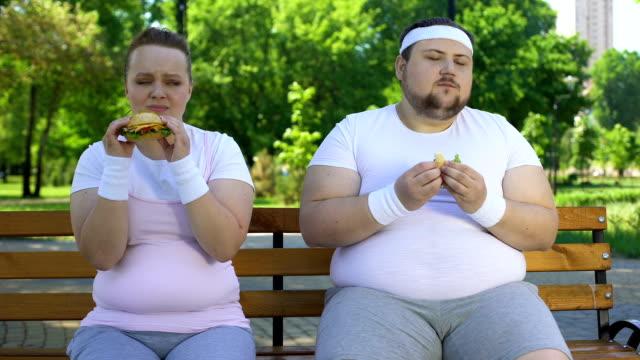 stockvideo's en b-roll-footage met vet jong koppel eten van hamburgers, verslaafd aan junk food, gebrek aan wilskracht - ongezond leven